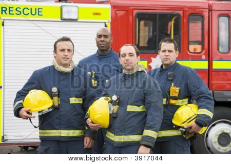 Four Firefighters Standing By Fire Engine