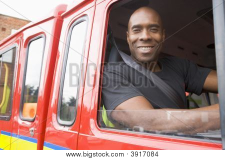 Fireman Sitting In Fire Engine Looking Out Window