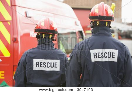 Two Rescue Workers Standing Near Rescue Vehicle