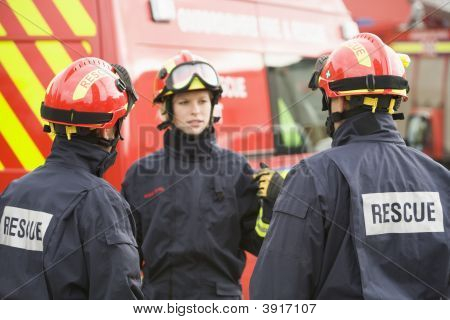 Three Rescue Workers Talking By Rescue Vehicle (Selective Focus)
