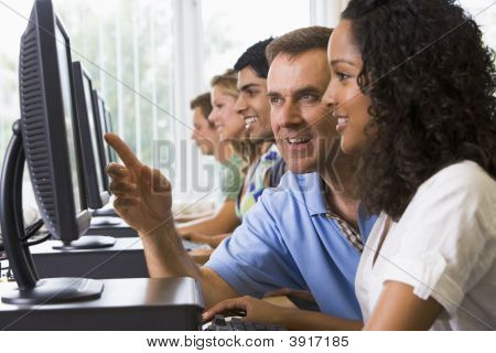 Four Students Sitting At Computer Terminals With Teacher Helping One Of Them (Depth Of Field/High Ke