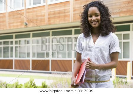 Student Standing Outdoors Smiling And Holding Binder