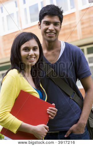 zwei Studenten ständigen lächelnd outdoors