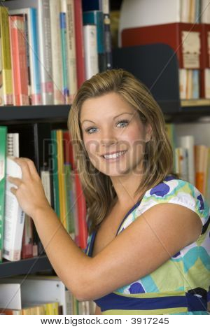 Student In Library Pulling Book Off Shelf