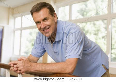 Teacher In Corridor Leaning On Railing