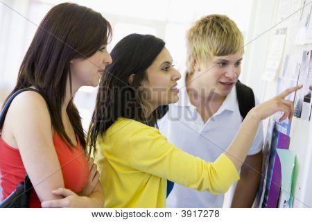 Three Students In Corridor Looking At Bulletin Board (High Key)