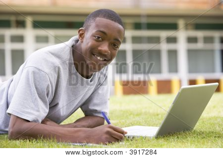 Student Lying Outdoors On Lawn With Laptop