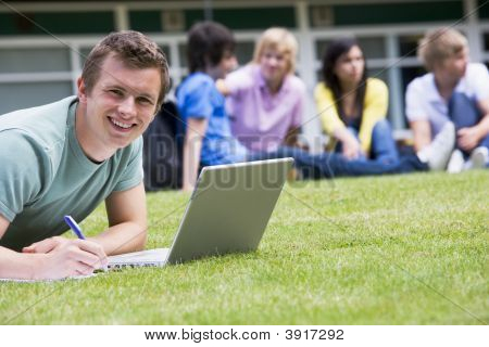 Student Outdoors On Lawn Using Laptop With Other Students In Background (Selective Focus)