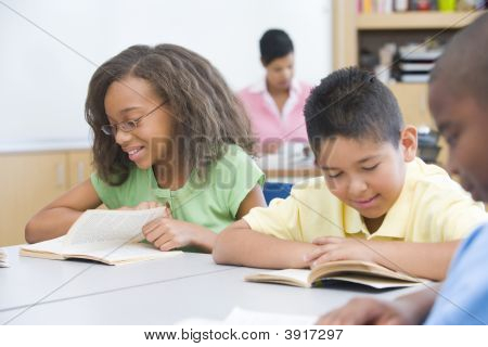 Students In Class Reading With Teacher In Background (Selective Focus)