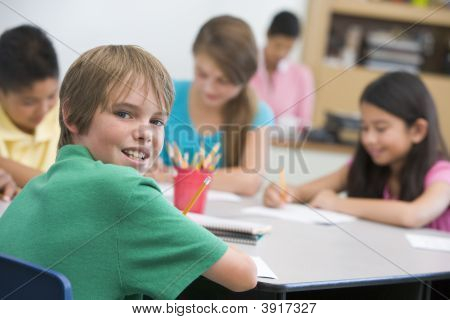 Students In Class Writing With Teacher In Background (Selective Focus)