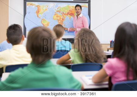 Students In Class With Teacher At Front Showing Map (Selective Focus)