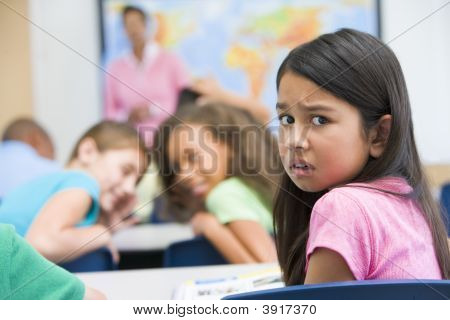 Student In Class Being Bullied By Students In Background (Selective Focus)