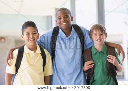 Three Students Standing Outside School Together Smiling (High Key)