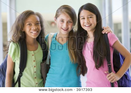 Three Students Standing Outside School Together Smiling (Selective Focus)