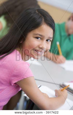 Estudiante en clase mirando a cámara (enfoque selectivo)