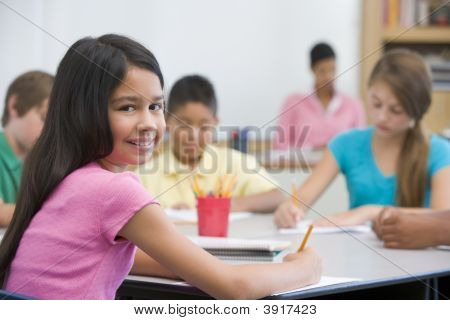 Students In Class Taking Notes With Teacher In Background (Selective Focus)