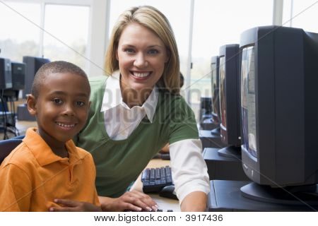 Teacher Sitting With Student At Computer Terminal With Students In Background (Selective Focus/High