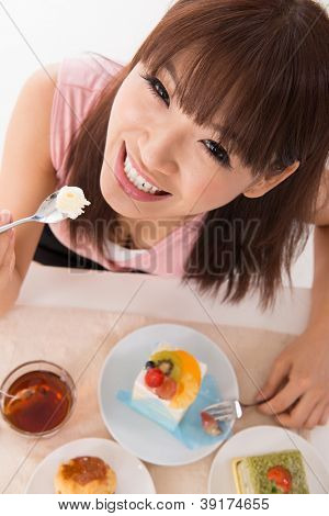 Pretty Asian woman eating cake.