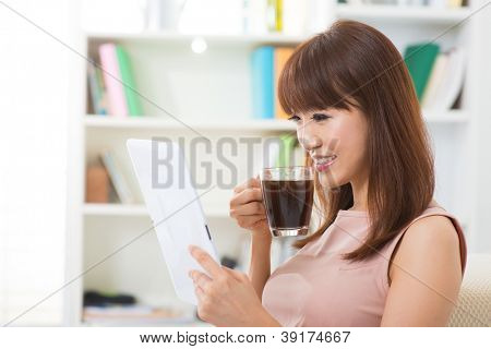Asian female enjoying cup of coffee and digital tablet inside house