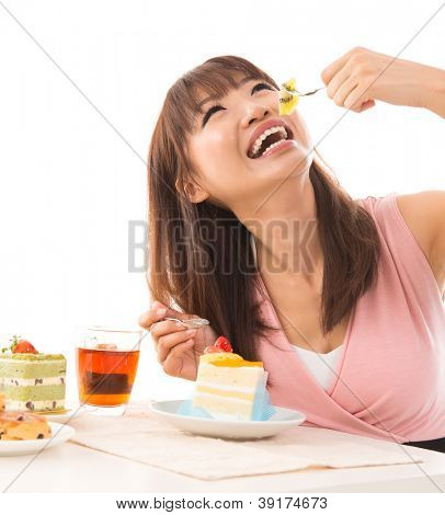 Smiling Asian woman eating cakes in the living room in her house