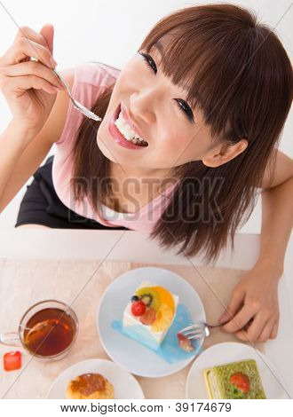 Fun Asian woman eating the cake inside house
