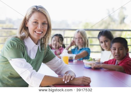 Teacher Sitting At Table Outdoors With Students Eating Lunch In Background (Depth Of Field)
