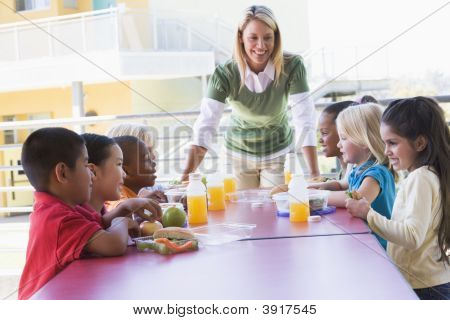 Teacher Leaning On Table Outdoors While Students Eat Lunch (High Key)