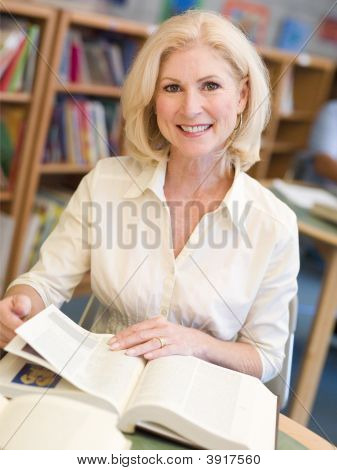 Woman Sitting In Library With A Book (Selective Focus)