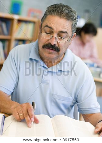 Man Sitting In Library With A Book And Notepad (Selective Focus)