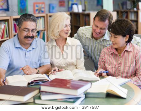 Three People Sitting In Library With Books And Notepads While A Man Leans Over Them (Selective Focus