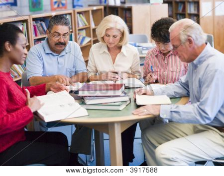 Five People Sitting In Library With Books And Notepads (Selective Focus)