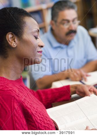 Woman Sitting Near Man In Library With Books And Notepads (Selective Focus)
