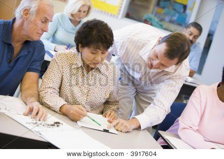Teacher In Class Helping Adult Students (Selective Focus)