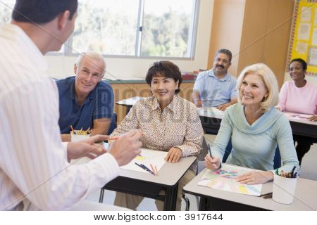 Adult Students In Class Drawing Pictures With Teacher In Foreground (Selective Focus)