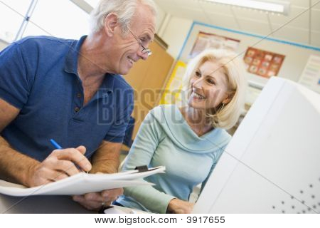 Two People At Computer Terminal With Notepad