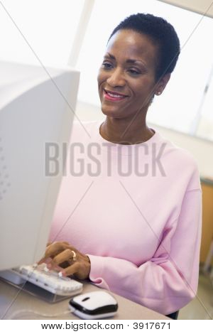 Woman At Computer Smiling And Looking At Monitor (High Key)