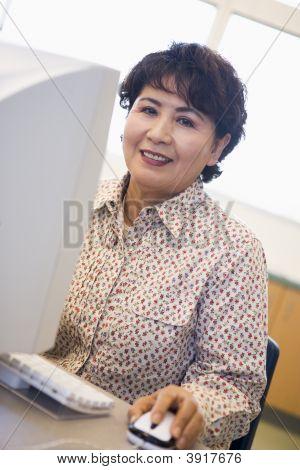 Woman At Computer Smiling And Looking At Monitor (High Key)