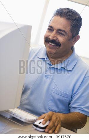 Man At Computer Smiling And Looking At Monitor (High Key)