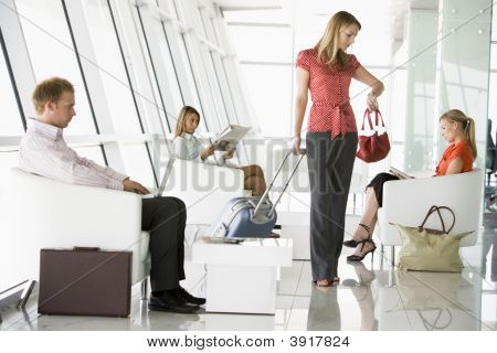 Female Airline Passenger Waiting With Other Passengers In Departure Gate