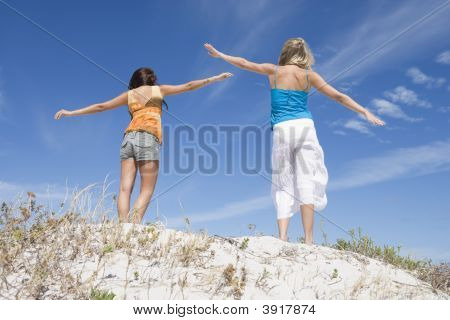 Two Young Women Posing On A Sand Hill