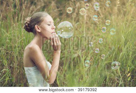 Retrato de la hermosa rubia empieza pompas de jabón en el campo