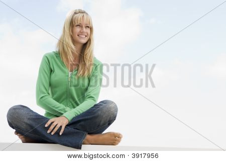 Blonde Woman In A Green Sweater Sitting Outdoors