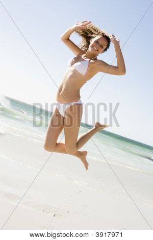 Woman In A Two Piece Bathing Suit Jumping On A Beach