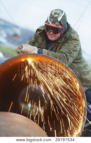 Construction Welder worker in protective glasses cutting metal pipe at building site with welding flame torch cutter