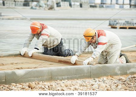 Two construction workers preparing ground base foundation for paving tile sideway