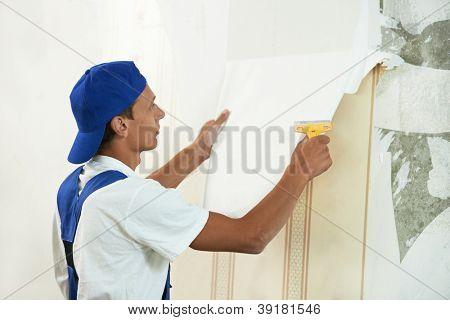 Trabalhador de um pintor descascando a parede durante o trabalho de renovação interior de reparo home