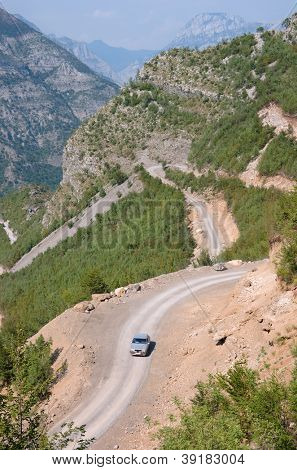 car is traveling uphill the winding dirt road between the albanian mountains down into the Kelmend Valley