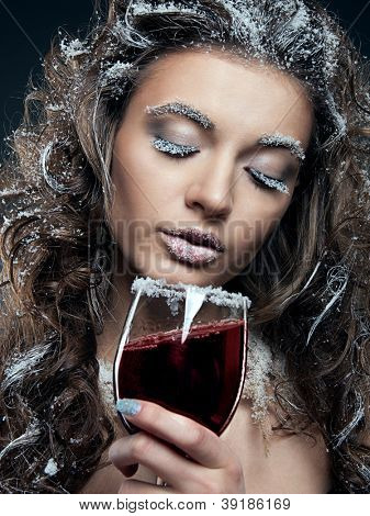 Portrait of young woman with snow make-up with a glass of wine. Christmas snow queen