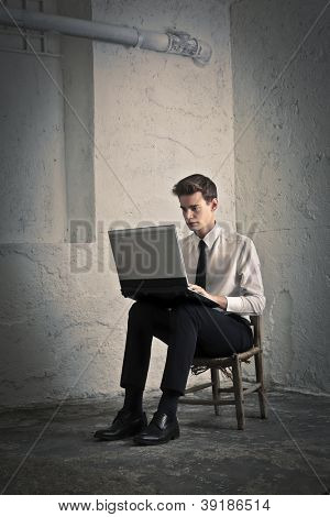 Young man in tie using a laptop computer on a chair in a basement