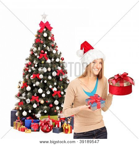 Happy female wearing christmas hat and holding gifts, christmas tree in the background